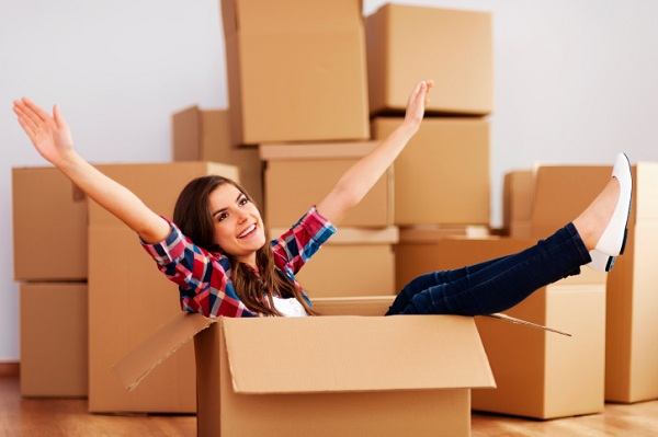Cheerful woman sitting in a cardboard box