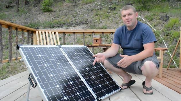 man standing near solar panel