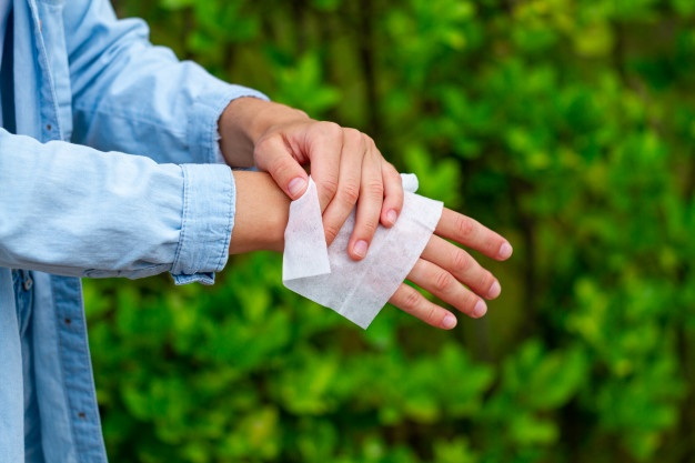 man cleaning his hands with wet wipe