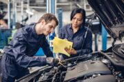 Auto car repair service center. Two mechanics - man and woman examining car engine