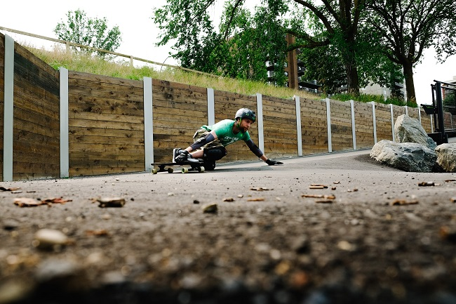 picture of a man on skateboard in a park wearing skateboard wrist guard and other skateboard protective gear