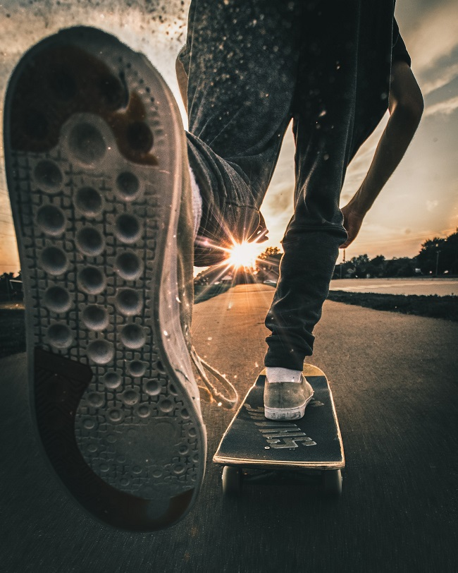 picture of a man on skateboard driving on the road to sunset with the best skateboarding shoes