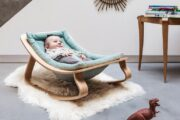 picture of a baby in a wooden bouncer seat