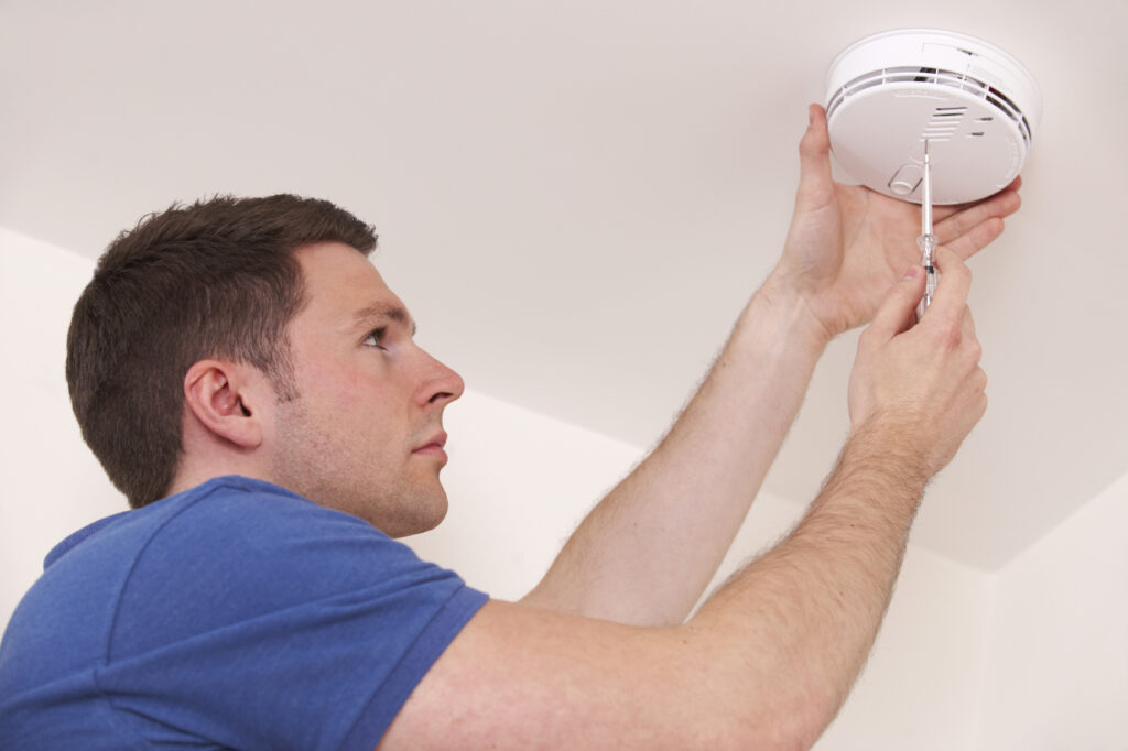 man installing smoke detector device