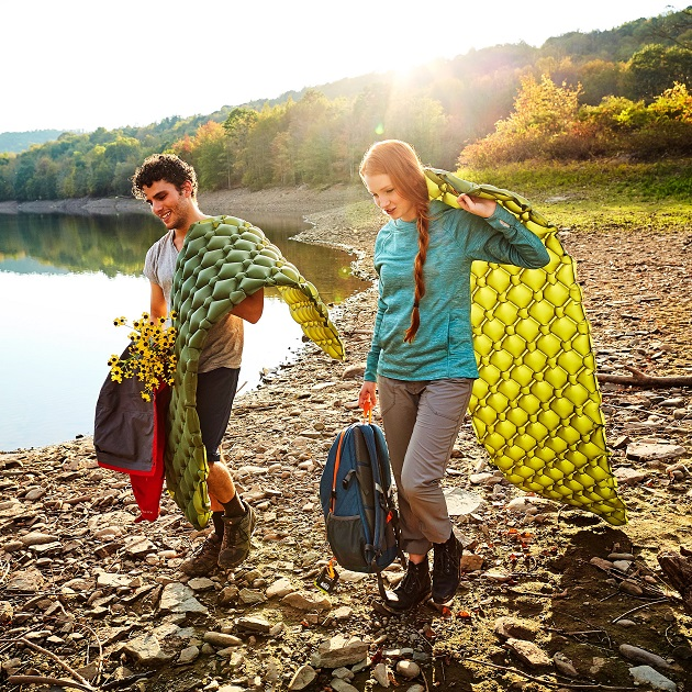 two people carrying sleeping mats for camping near lake